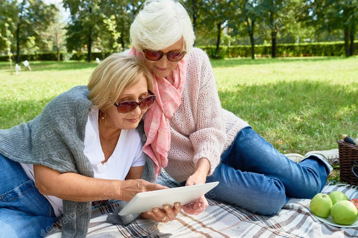 Two Senior Women Using Digital Tablet in Park
