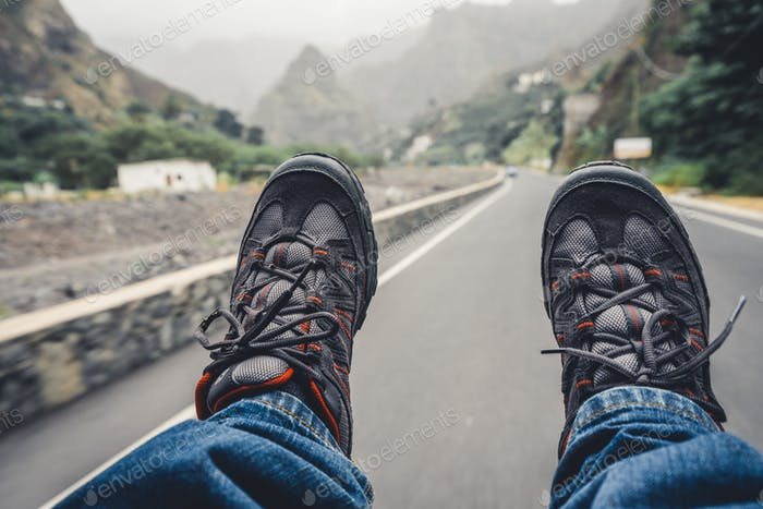 Relaxing feet with trekking footwear hanging from pickup car after long trek way. Santo Antao Island