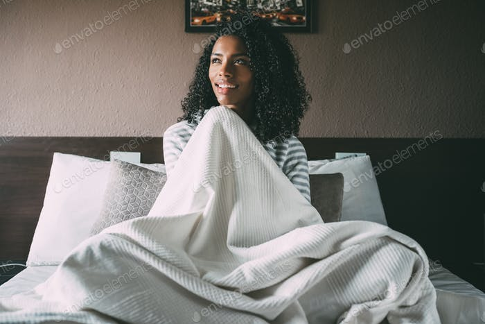 Pretty black woman covered with sheet and sit on bed looking away