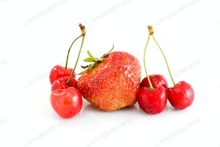 Einzel leckere rote Erdbeere und einige saftige rote Kirschen
