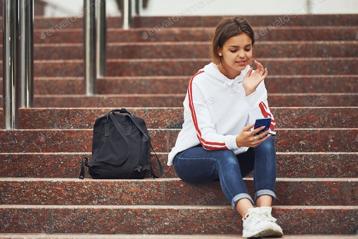 Positive female student sitting on stairs outdoors with smartphone at daytime