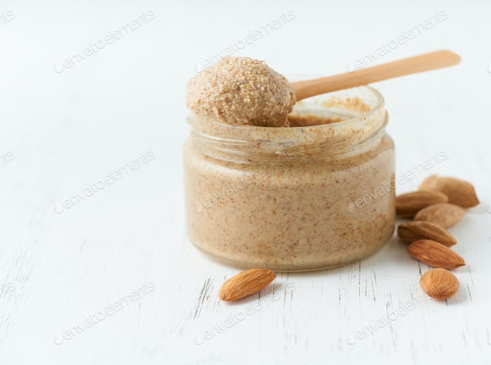 Almond butter, raw food paste made from grinding almonds, glass jar, side view, close up