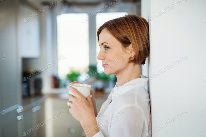 A young woman with cup of coffee standing indoors, leaning on a wall.