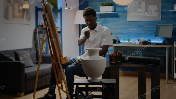 Artist of african american ethnicity analyzing vase