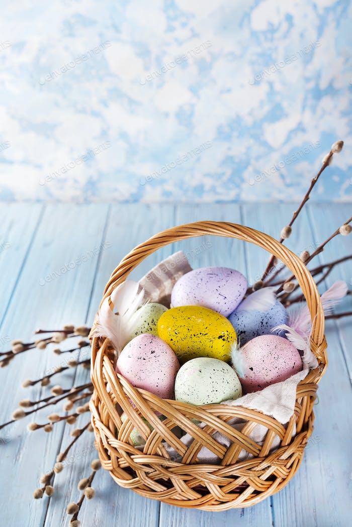 Osterkorb gefüllt mit bunten Eiern auf blauem Hintergrund
