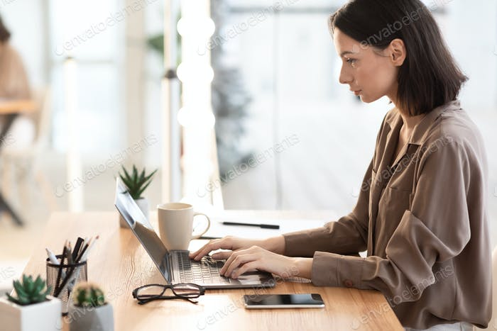 Woman working with laptop at modern office