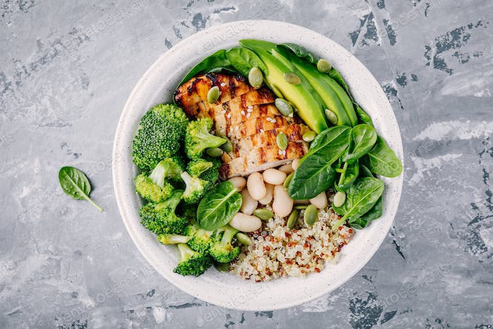 Green buddha bowl lunch with grilled chicken and quinoa, spinach, avocado, broccoli and white beans