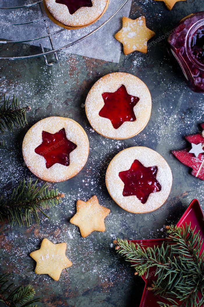 Christmas Linzer cookies with raspberry jam on green table background. Top view