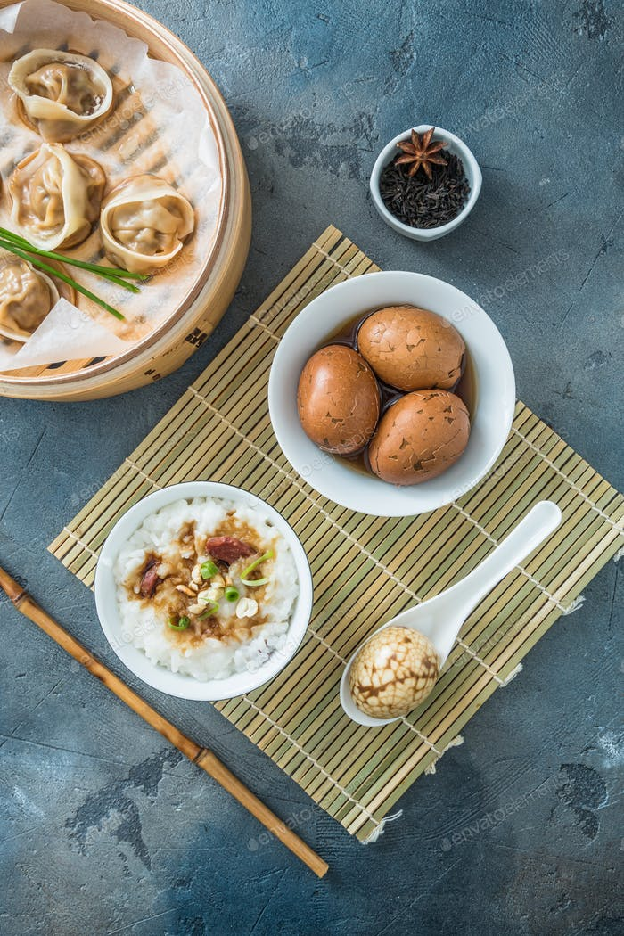 Chinese breakfast with rice porrige, tea eggs and dim sum