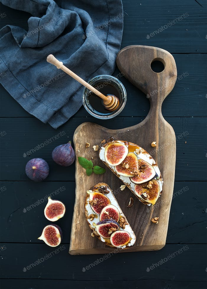Sandwiches with ricotta, fresh figs, walnuts and honey on rustic wooden board over black backdrop