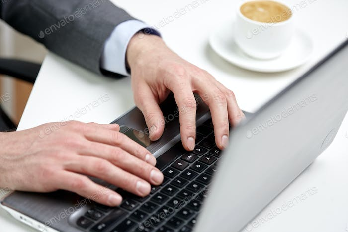 close up of male hands with laptop and coffee cup