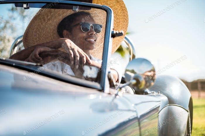 Black woman driving a vintage convertible car
