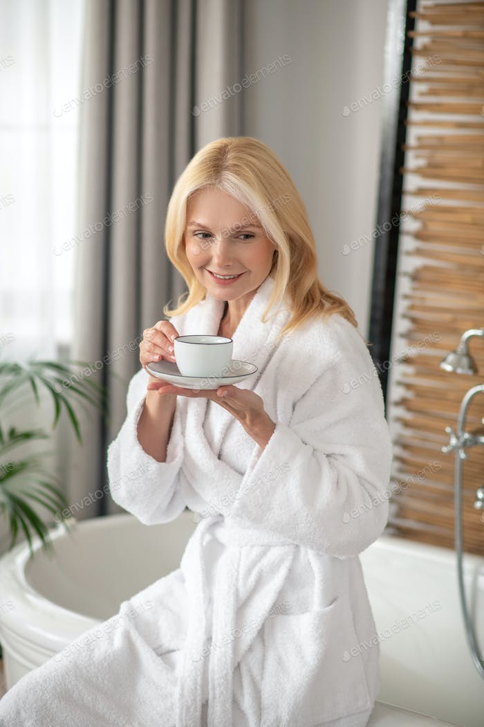 Good-looking blonde woman having tea and looking balanced