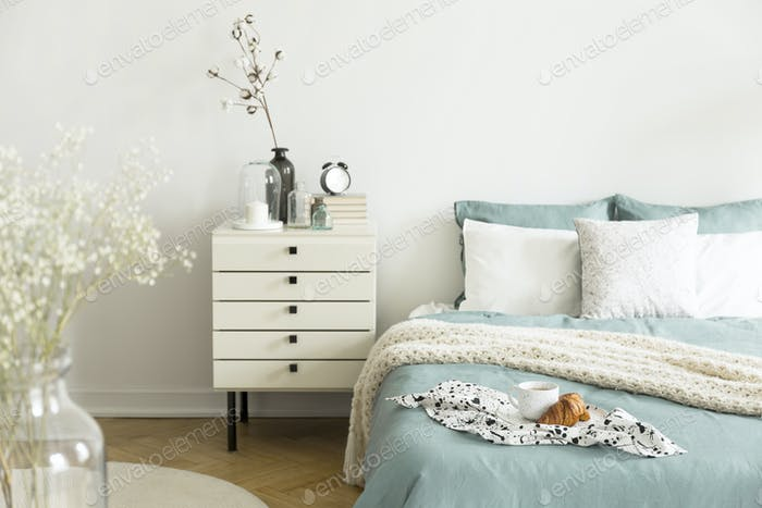 A bright bedroom interior with sage green and white bedding, pil