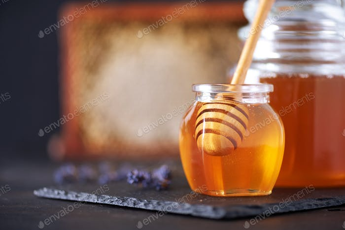 Herbal honey with lavender flowers, bee pollen granules, honey conb on black background. Autumn