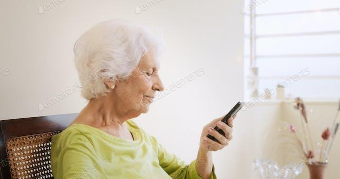 Glückliche alte Frau mit Handy für Freizeit