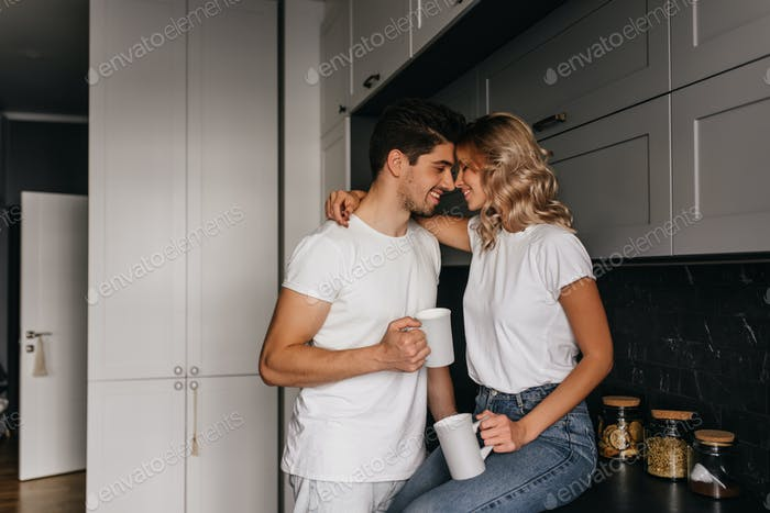Charming curly girl embracing husband during breakfast.