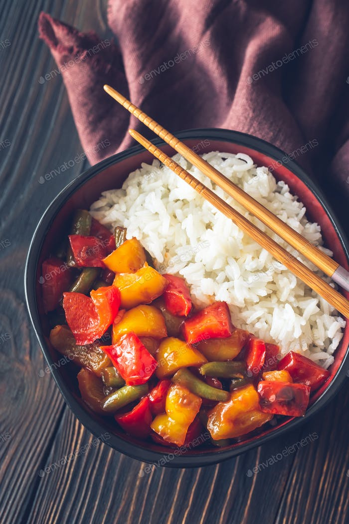 Bowl with white rice and fried vegetables