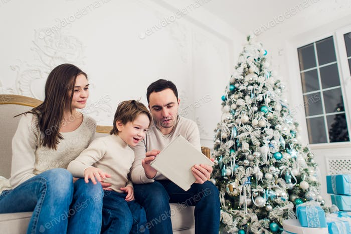 christmas, x-mas, winter, happiness, technology and people concept - smiling family with tablet pc
