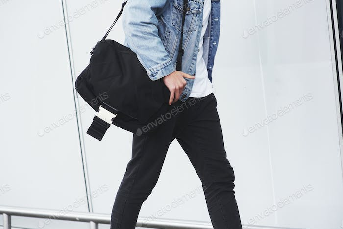 Young handsome man with a bag on his shoulder in a hurry to the airport