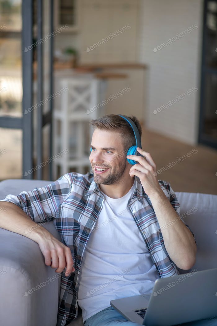 A young man listening to music and smiling