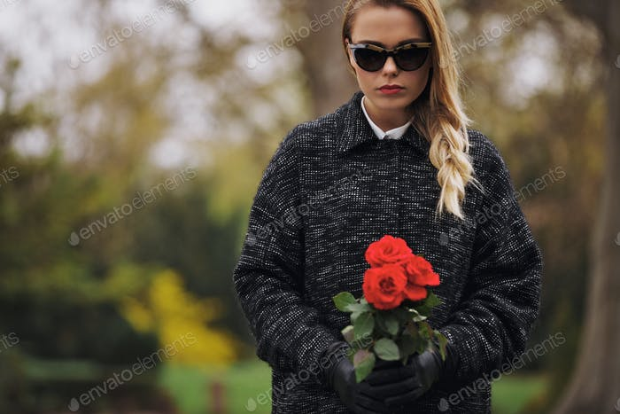 Junge Frau auf dem Friedhof mit frischen Rosen