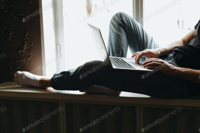 Young man typing something on a laptop