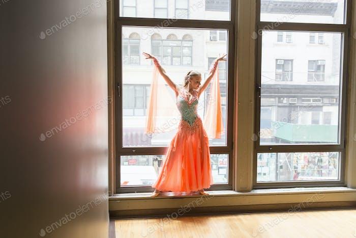 Dancer in dance studio. A woman posing at a window.