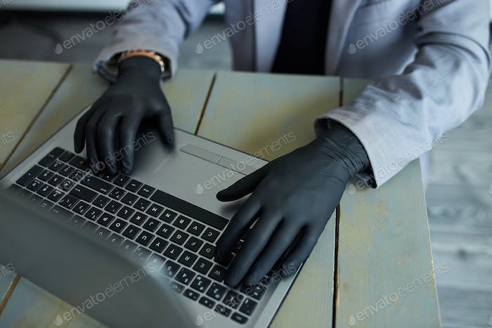 Man working from home at notebook, wearing black disposable gloves for protection.