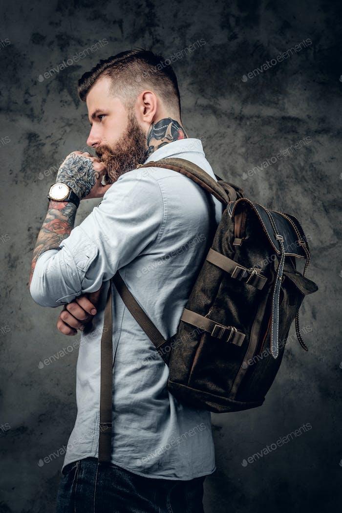 Bearded tattooed backpacker posing in studio.