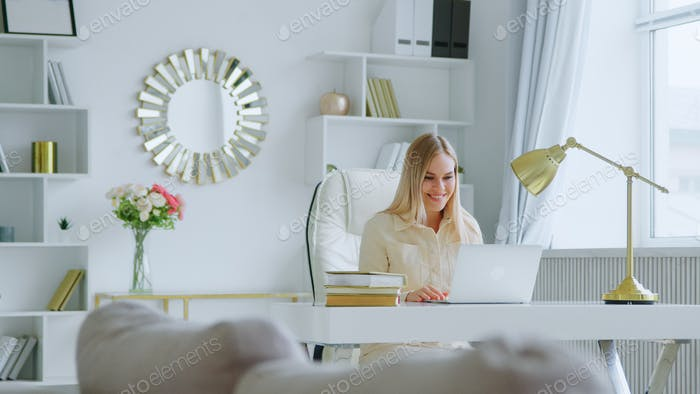 Young attractive woman holding video conference remotely