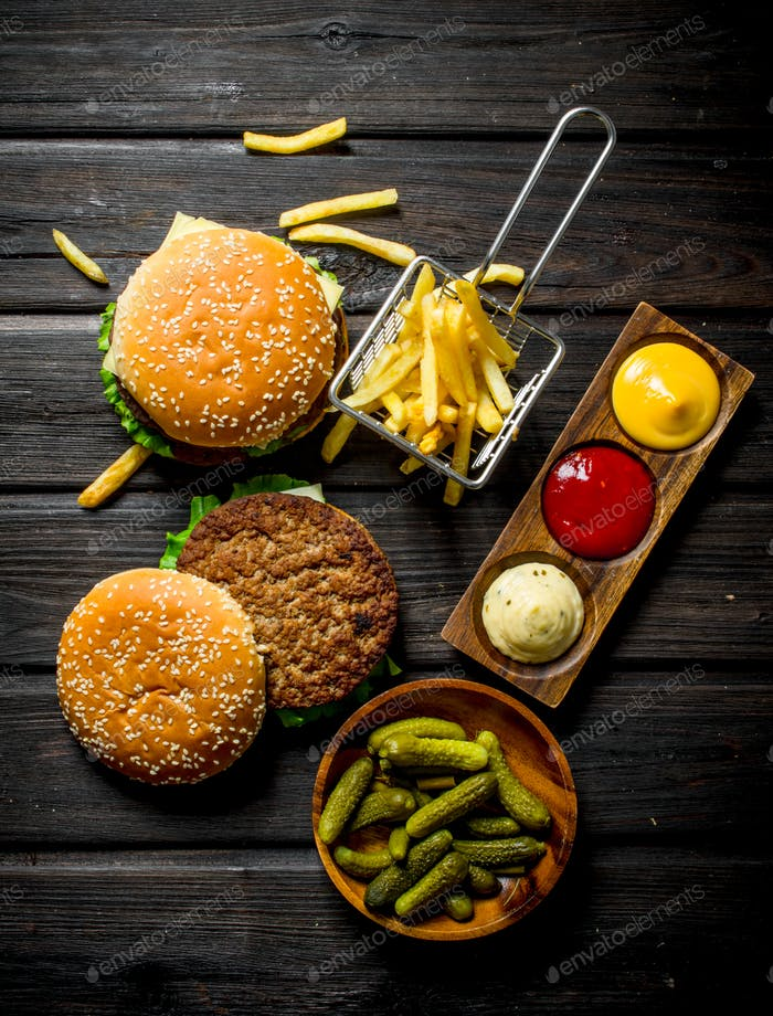 Burgers with gherkins in bowl,French fries and sauces.