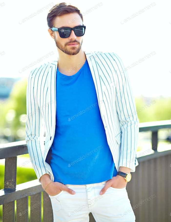hipster handsome man in stylish summer white suit posing on street background in sunglasses
