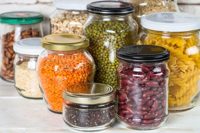 Getreide, Hülsenfrüchte und Bohnen in Gläsern auf weißem Küchentisch