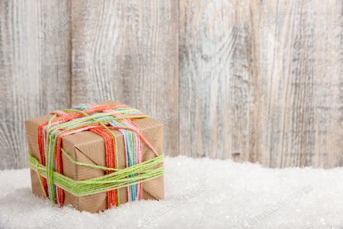 Gift box for Christmas and New Year holidays on snow, copy space