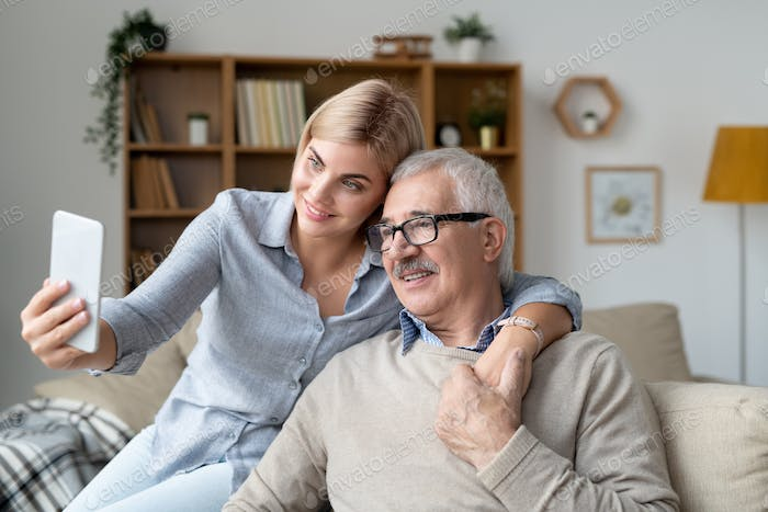 Happy young woman with smartphone embracing senior father while making selfie