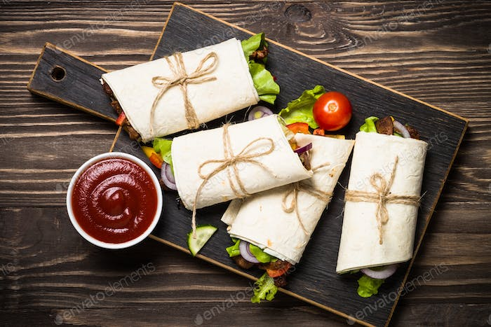 Burritos tortilla wraps with beef and vegetables on wooden background.