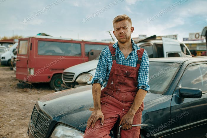 Male repairman poses on car junkyard