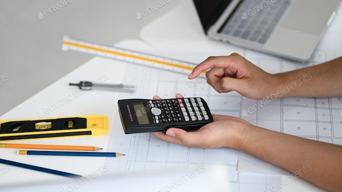 Mano usando en la calculadora, los ingenieros usan una calculadora para calcular los planos de la casa.
