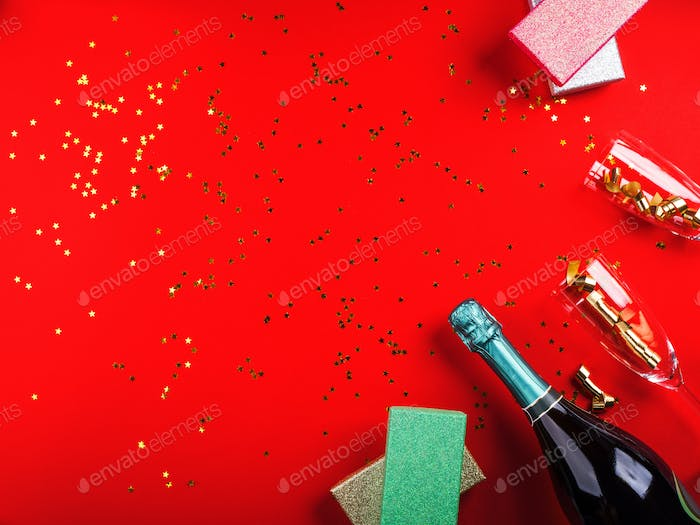 Champagne, gifts and flute on red with confetti