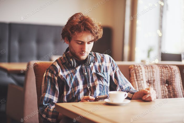 Young man freelancer with a beard in everyday clothes sitting in a cafe with a cup of coffee