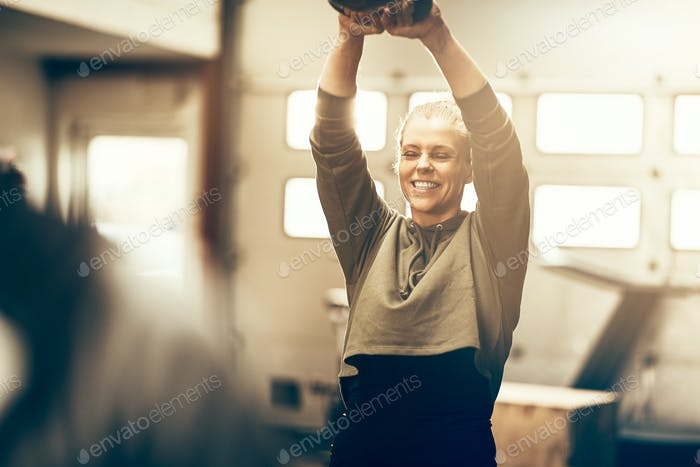 Smiling young woman swinging a dumbbell at the gym