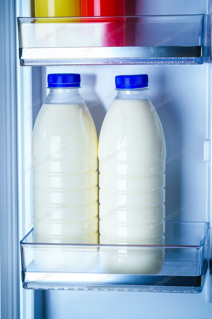 Bottles of milk in the fridge