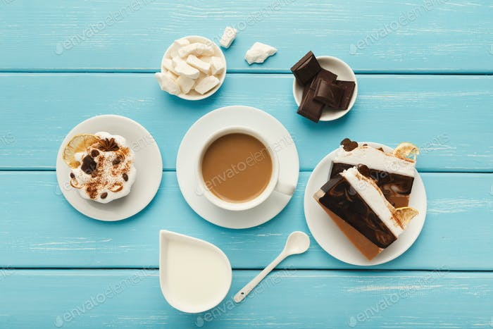 Coffee cup and sweets on blue vintage wooden table, top view