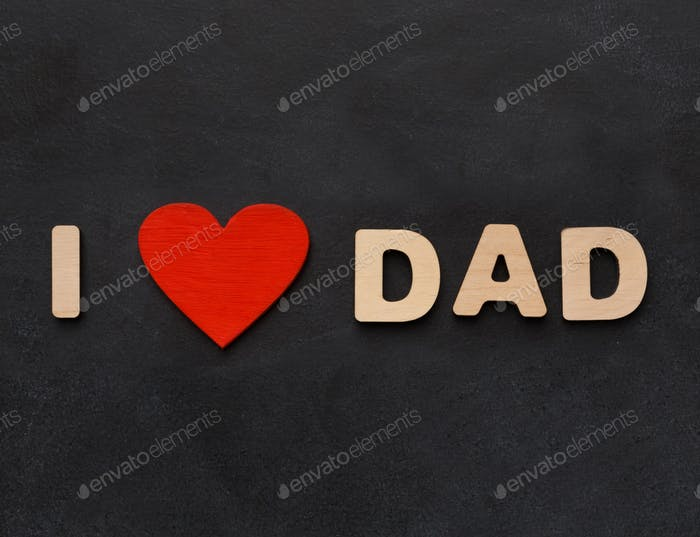 Love dad phrase written on black with wooden letters