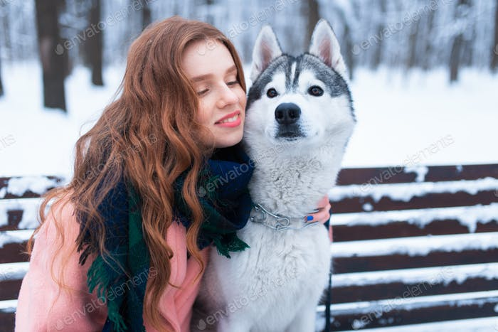 Happy woman sitting on the bench with husky