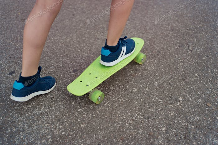 Close up of skateboarder feet while skating in the park