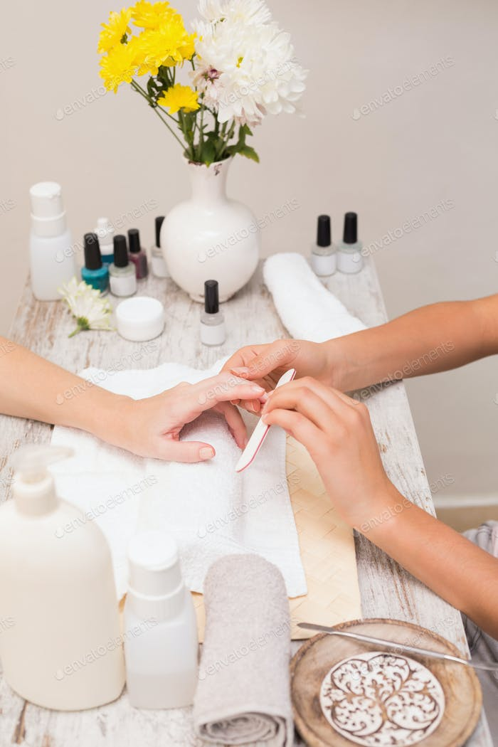 Nageltechniker geben Kunden eine Maniküre im Schönheitssalon