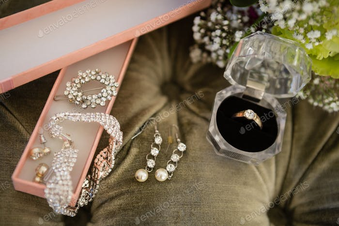 High angle view of bride jewelry on sofa