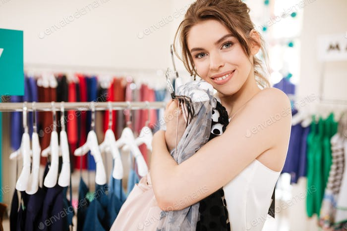 Portrait of smiling girl in white top happily looking in camera and hugs dresses in clothing store
